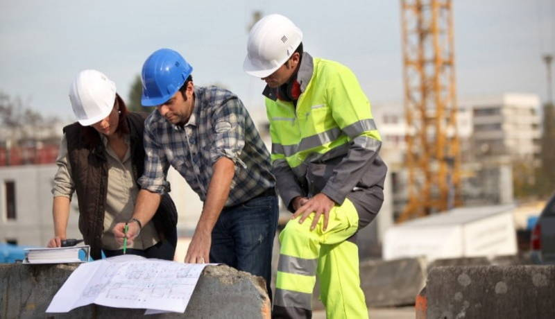 Three engineers working on the construction site.